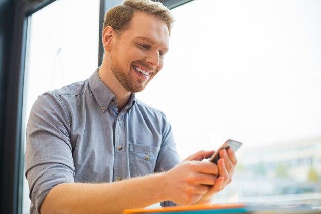 Allegro uomo felice felice guardando lo schermo dello smartphone e sorridente durante l'utilizzo di questo dispositivo