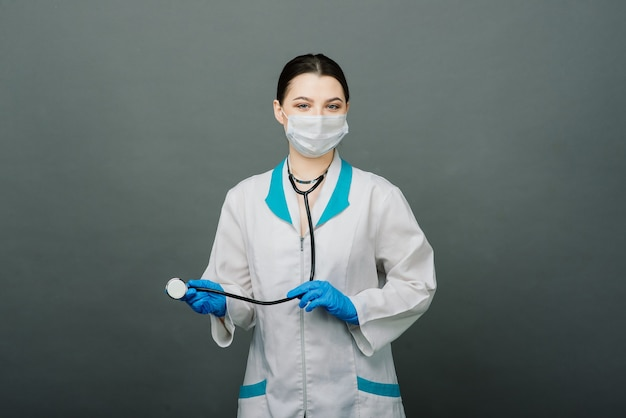 Allegro medico felice con le mani incrociate su sfondo grigio