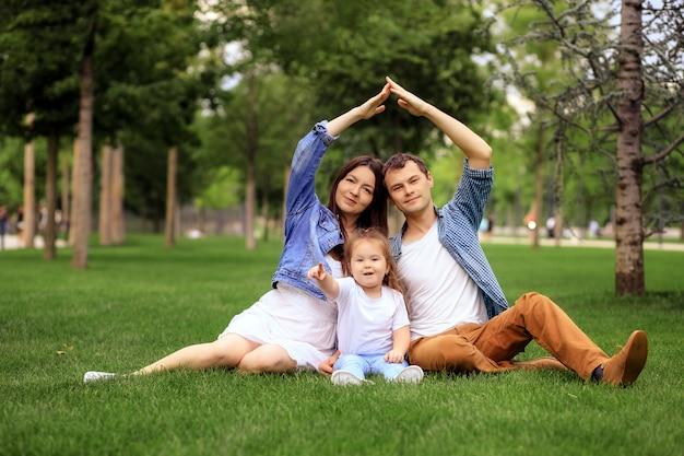 Famiglia felice allegra che abbraccia e che guarda l'obbiettivo mentre riposa sull'erba verde in giornata di sole nel parco