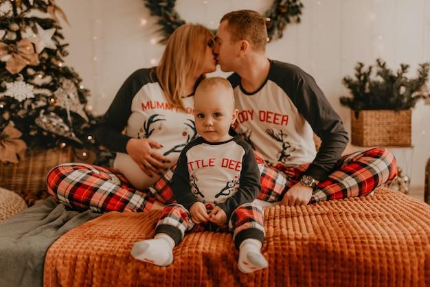 Allegra famiglia felice in pigiama con un bambino che bacia sul letto in camera da letto. i vestiti di famiglia del nuovo anno sembrano abiti. regali di celebrazione di san valentino