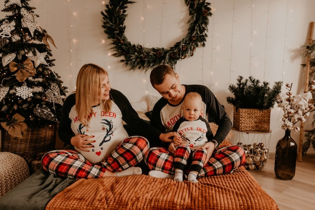 Allegra famiglia felice in pigiama con bambino si trovano sul letto in camera da letto. i vestiti di famiglia del nuovo anno sembrano abiti. regali di celebrazione di san valentino