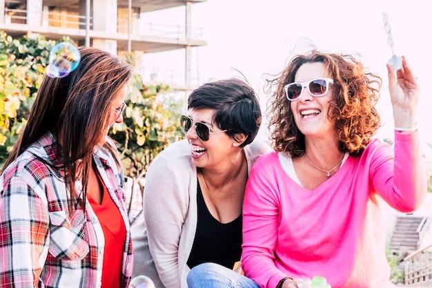 Gruppo allegro e felice di amici yong donna che si diverte insieme in amicizia giocando e ridendo con le bolle di sapone - ridendo molto in attività ricreative all'aperto per femmine caucasiche