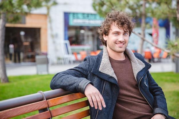 Allegro felice contenuto gioioso riccio giovane maschio in giacca nera seduto e riposato sulla panchina nel parco