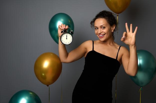 La donna allegra felice della corsa mista tiene la sveglia, è mezzanotte, mostrando i sorrisi del segno ok che guarda l'obbiettivo, isolato su sfondo grigio con palloncini. anno nuovo, concetto di buon natale per la pubblicità