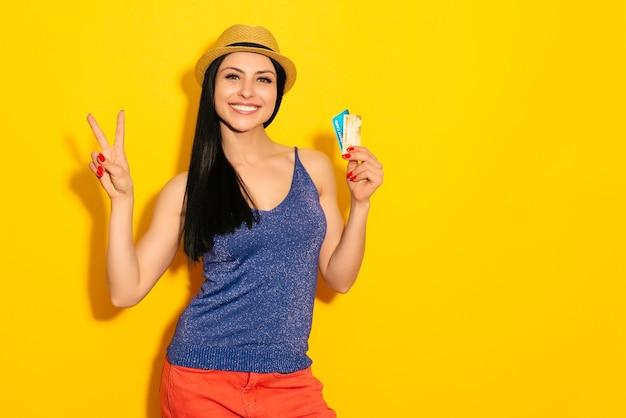 La giovane donna sorpresa felice allegra con la carta di credito che mostra canta la vittoria