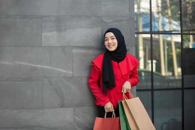 Allegra donna felice che si gode lo shopping sta portando le borse della spesa shopping