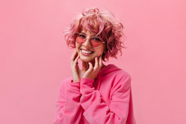 La donna felice allegra in occhiali da sole rosa posa sulla parete isolata