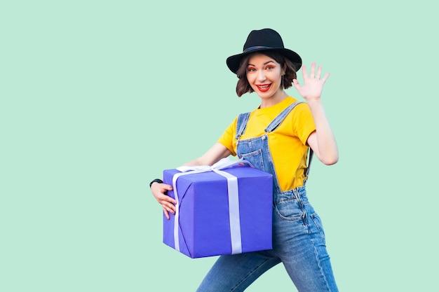 Allegra ragazza felice in pantaloni a vita bassa indossare in tuta di jeans e cappello nero in piedi e cercando di tenere in mano una scatola regalo gigante e pesante e ti saluta, mostrando cinque. studio girato, sfondo verde, isolato