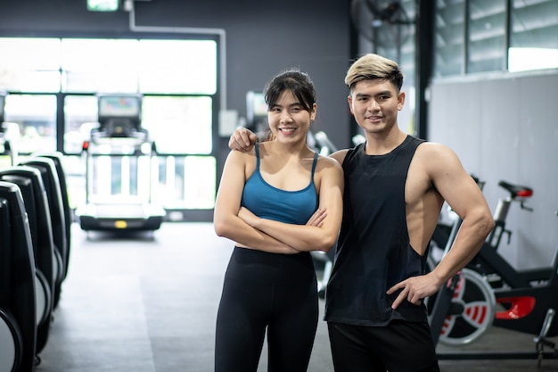 Allegro ritratto di sportivi asiatici sani in una palestra con copyspace. asian giovane sportiva e sportivo in posa per una fotografia in una palestra coperta. benessere e benessere nel concetto di persone sane.