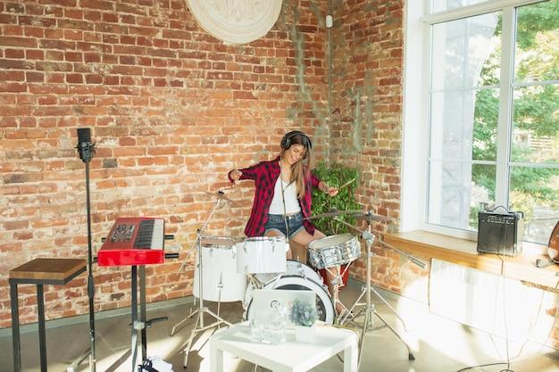 Allegro. studio musicale domestico, bella donna che registra musica, canta e suona la batteria mentre è seduta sul posto di lavoro in soppalco oa casa. concetto di hobby, musica, arte e creazione. creazione del primo singolo.