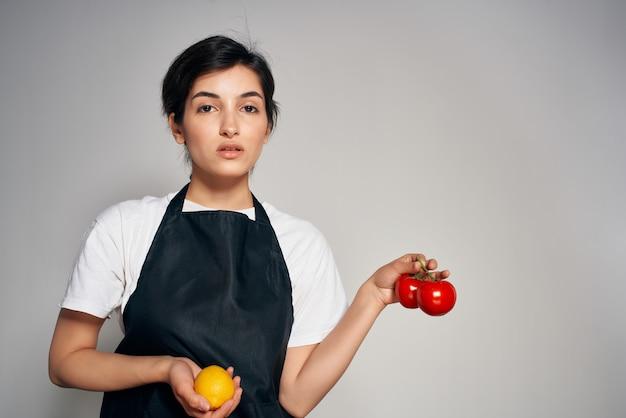 Casalinga allegra in cucina di cibo di verdure grembiuli neri