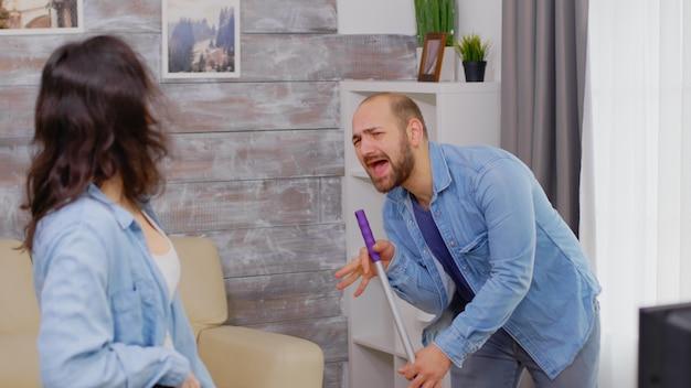 Marito e moglie allegri che cantano mentre puliscono la casa
