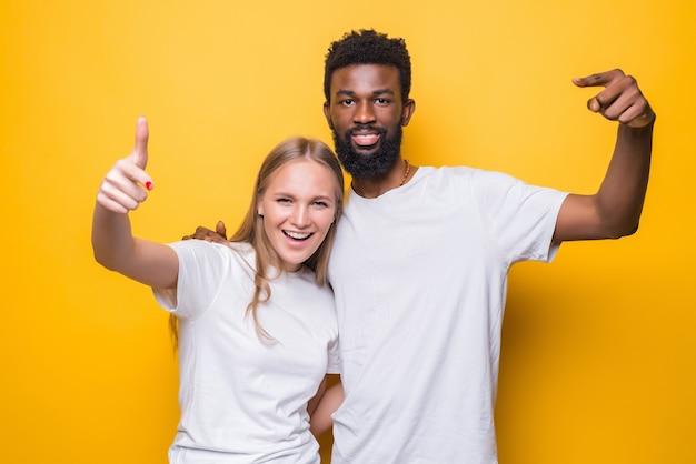 Allegra coppia interrazziale che scatta insieme un autoritratto, guarda la macchina fotografica e sorride, posando sul muro giallo