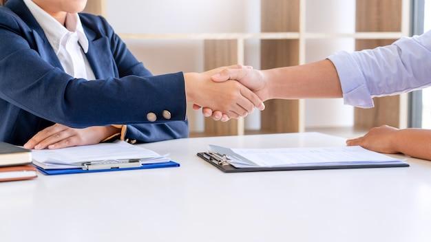 Allegro intervistatore responsabile delle risorse umane che accoglie le donne richiedente durante il colloquio di lavoro handshake