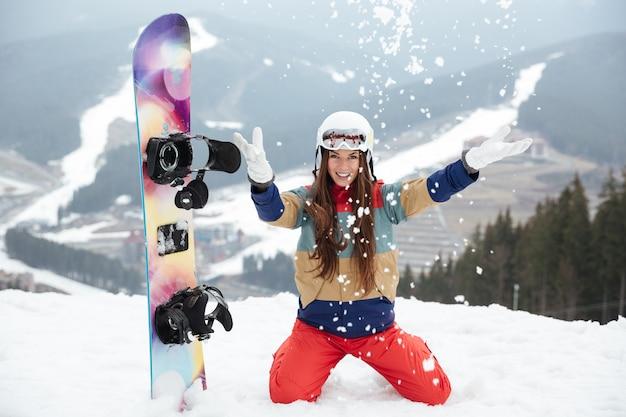 Snowboarder signora allegra sulle piste gelida giornata invernale
