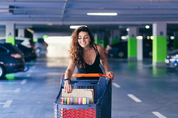 Signora allegra in vestito nero alla moda che trasporta sulle borse della spesa colorate in un parcheggio vicino a un'auto.