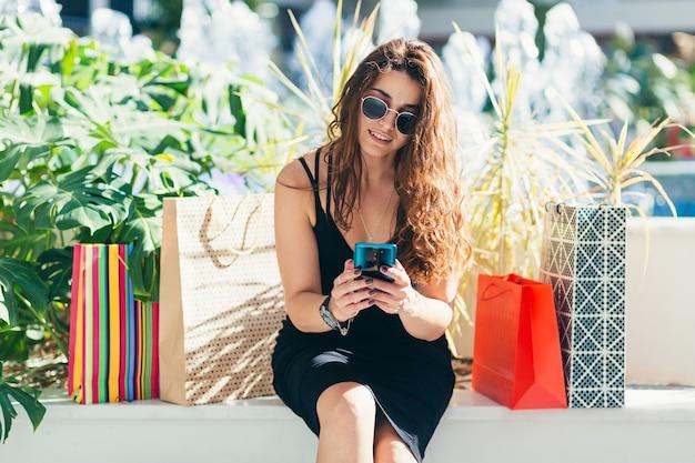 Signora allegra in vestito nero alla moda che porta sulle borse della spesa colorate mentre si cammina in negozio
