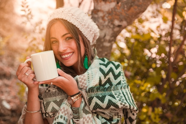 Signora allegra con la tazza nella foresta