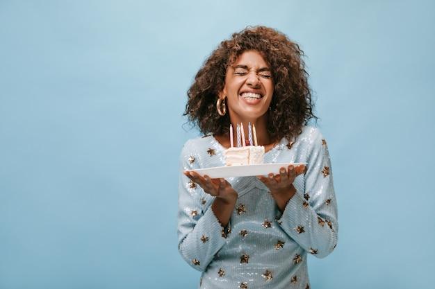Signora allegra con l'acconciatura ondulata in bei vestiti lucidi che si rallegra e tiene in mano un pezzo di torta con candele sulla parete blu