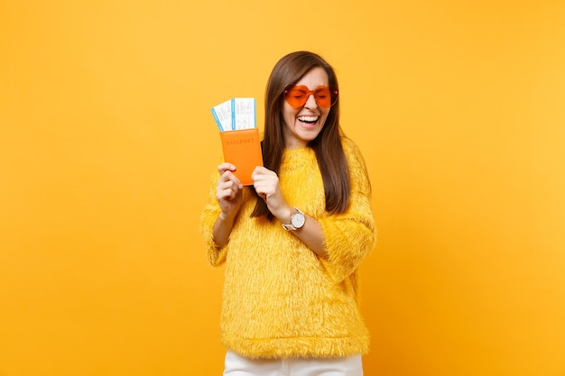 Giovane donna allegra che ride con gli occhi chiusi in occhiali a cuore arancione che tengono i biglietti della carta d'imbarco del passaporto isolati su sfondo giallo brillante. persone sincere emozioni stile di vita. zona pubblicità.