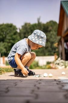 Ragazzino allegro che disegna campana con gesso a terra godendosi un'infanzia felice in cortile