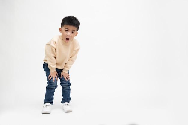 Allegro ragazzino esprime sorpresa faccia o wow isolato su sfondo bianco, modello di bambino asiatico felice, composizione di persone a lunghezza intera