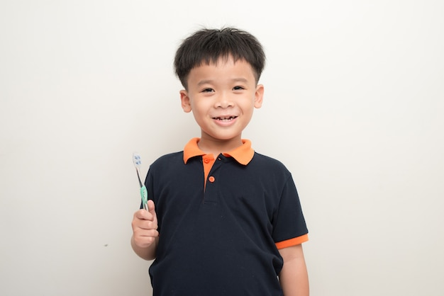 Ragazzino allegro che tiene uno spazzolino da denti su sfondo bianco, ritratto in studio di un ragazzo sano di razza mista con uno spazzolino da denti isolato.