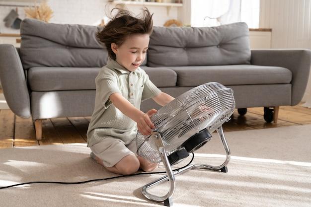Ragazzino allegro che si rinfresca con un grande fan a casa da solo il ragazzino gode di un forte soffio di vento fresco