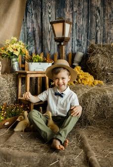 Allegro ragazzino in una camicia con un farfallino, un cappello di paglia e pantaloni si siede con gli anatroccoli sulla paglia contro la superficie di un pagliaio. stile rustico