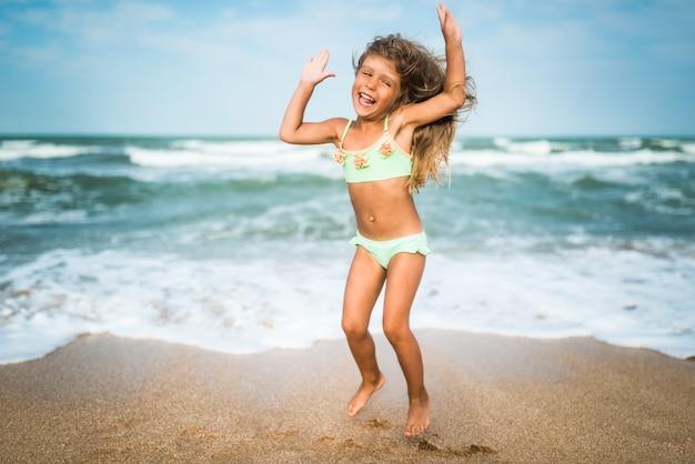 Piccola ragazza caucasica allegra che salta e che si diverte sulle onde del mare sulla costa sabbiosa nella soleggiata giornata estiva calda.