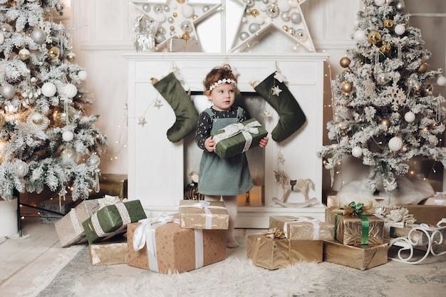 Il piccolo bambino allegro tiene un regalo di natale e si rallegra nell'atmosfera natalizia