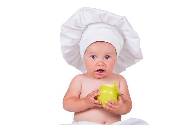 Piccolo bambino allegro con le mele nelle mani in un vestito del cuoco unico su un bianco.