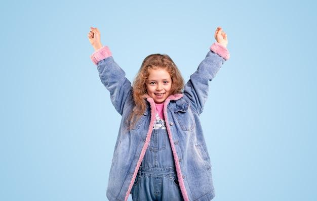 Bambina allegra in giacca di jeans caldo blu alzando le mani e guardando la fotocamera mentre in piedi su sfondo blu