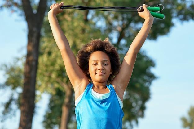 Bambina allegra che fa esercizio con la corda per saltare all'aperto