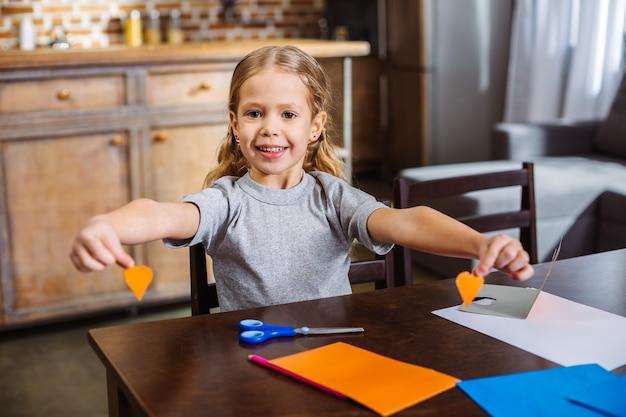 Bambina allegra che tiene i ritagli a forma di cuore mentre si gode l'artigianato