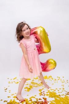 Una bambina allegra con un vestito rosa sta con un numero cinque gonfiabile multicolore su uno sfondo bianco con coriandoli