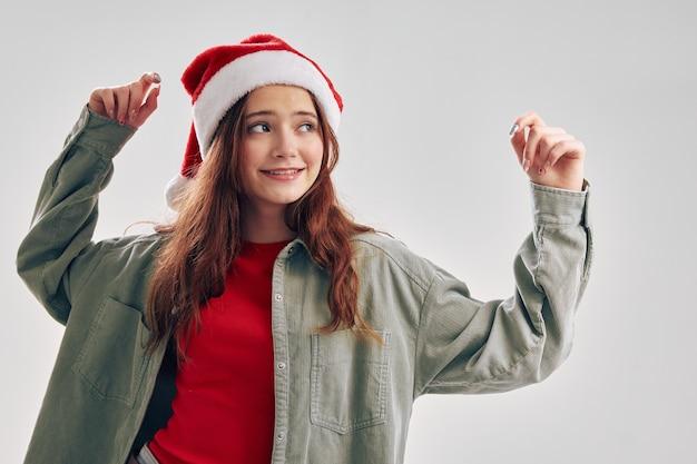 Bambina allegra in un cappello rosso che gesturing con il suo divertimento delle mani ballando il nuovo anno di natale. foto di alta qualità