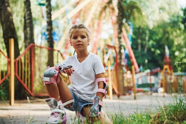 La bambina allegra sui pattini a rotelle si diverte nel parco vicino alle attrazioni