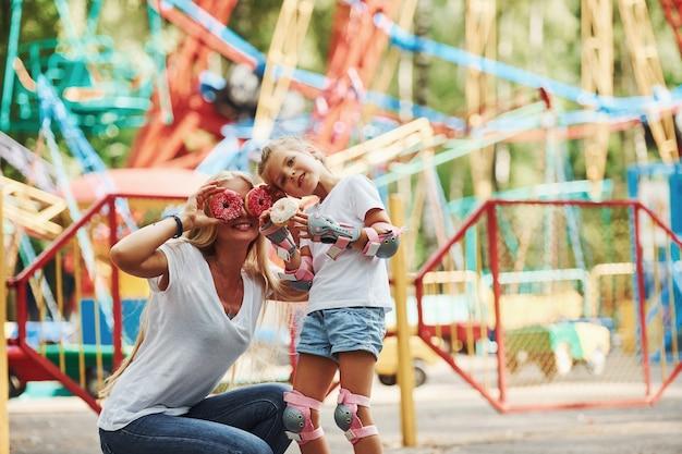 La bambina allegra sui pattini a rotelle e sua madre si divertono insieme nel parco vicino alle attrazioni