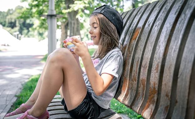 La bambina allegra si siede su una panchina con un telefono in estate.