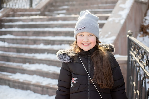 Bambina allegra in una passeggiata nel parco in inverno