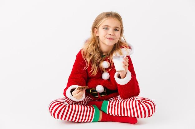 Bambina allegra che indossa il costume di natale seduto isolato, mangiando biscotto con latte