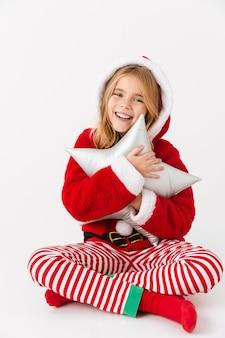 Bambina allegra che indossa il costume di natale seduto isolato, tenendo in mano un cuscino a forma di stella