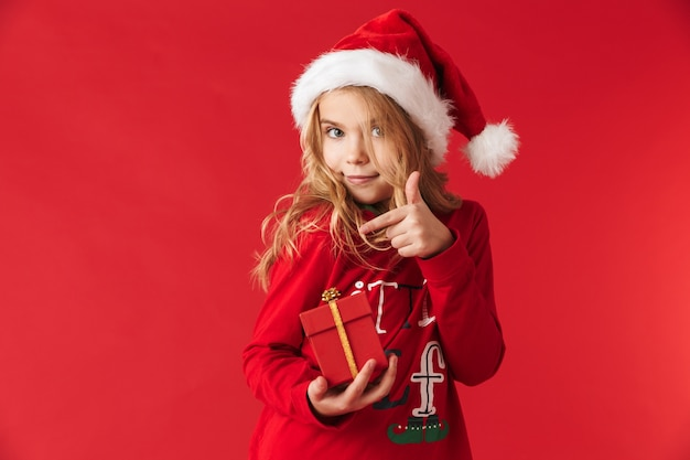 Bambina allegra che indossa il costume di natale in piedi isolato, tenendo i contenitori di regalo
