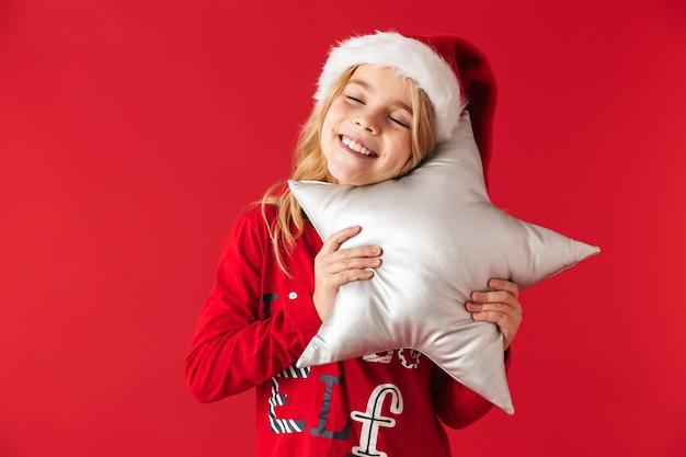 Bambina allegra che indossa il costume di natale in piedi isolato, tenendo in mano un cuscino a forma di stella