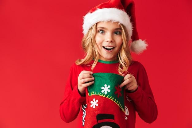 Bambina allegra che indossa il costume di natale in piedi isolato, prendendo i regali da un calzino di natale