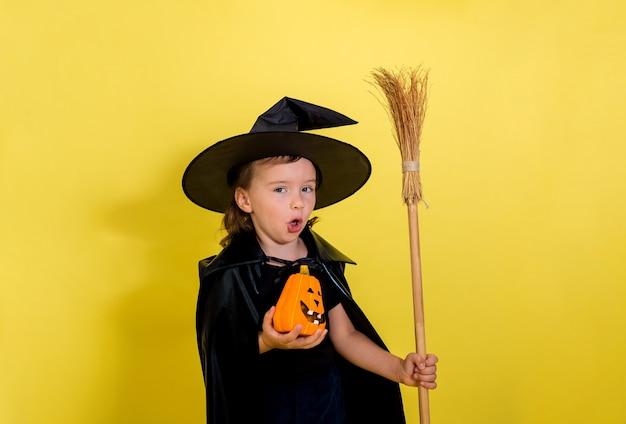 Una bambina allegra in un costume da strega con una zucca e una scopa su una parete isolata gialla