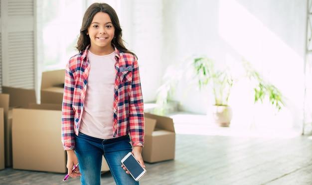 Allegra bambina con occhi scuri e capelli castani tiene una penna e un cellulare in piedi nella stanza con scatole di cartone sullo sfondo. concetto di trasloco