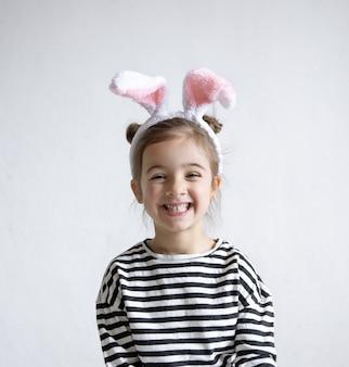 Bambina allegra con le orecchie del coniglietto di pasqua decorative sulla sua testa.