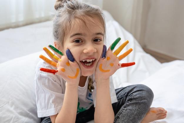 Bambina allegra con palme dipinte con sorrisi. creatività e arte dei bambini.